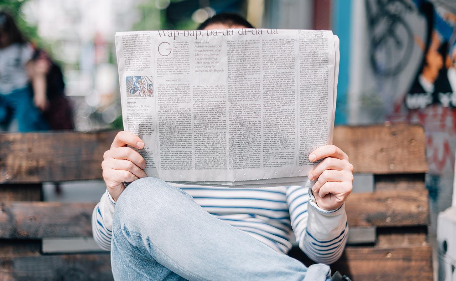 Man läser papperstidning. Foto: Roman Kraft / Unsplash